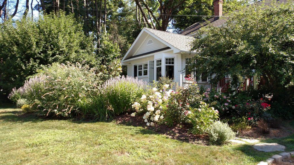 Maison avec jardin fleuri et arbustes sous un temps ensoleillé